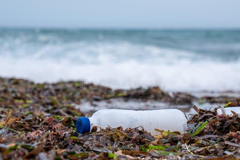 Plastic verontreinigingsoverzees, fles en afval op zand stock foto's