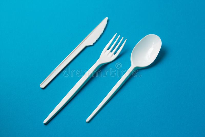 Plastic Vork, Lepel en Knive op Blauwe Achtergrond royalty-vrije stock foto's