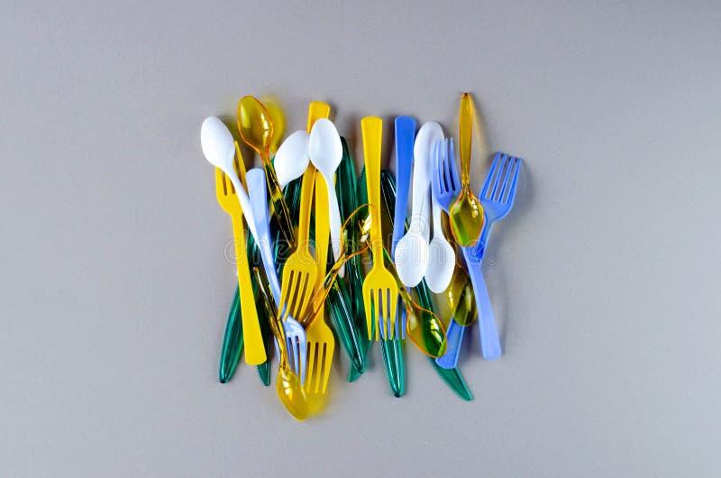 Plastic vorken, lepels en messen op een grijze achtergrond royalty-vrije stock afbeelding