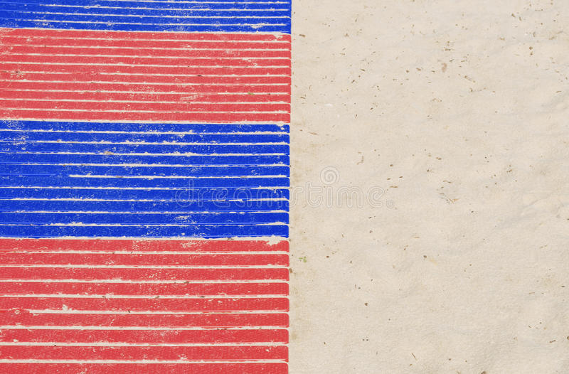 Plastic walkway on sandy beach. Blue and red plastic walkway on sandy beach stock photography
