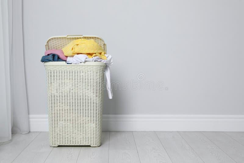 Plastic wasmandhoogtepunt van vuile kleren op vloer dichtbij lichte muur stock foto