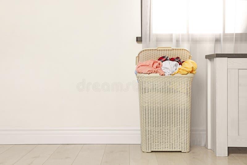 Plastic wasmandhoogtepunt van vuile kleren op vloer dichtbij lichte muur in ruimte stock afbeelding