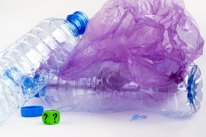 Plastic waste: bottles, polyethylene bags, dice with a question mark. stock photo