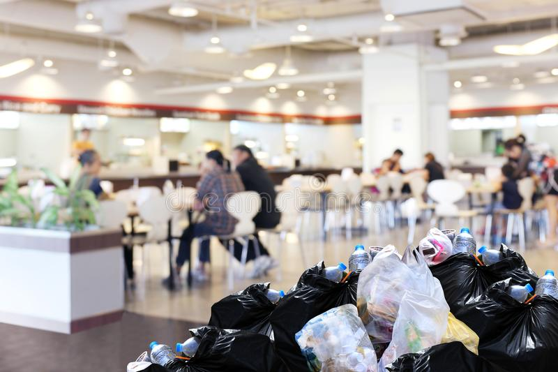 Plastic waste garbage bag black bin full Lots pile of junk at front canteen food court mall department store background, pollution royalty free stock image