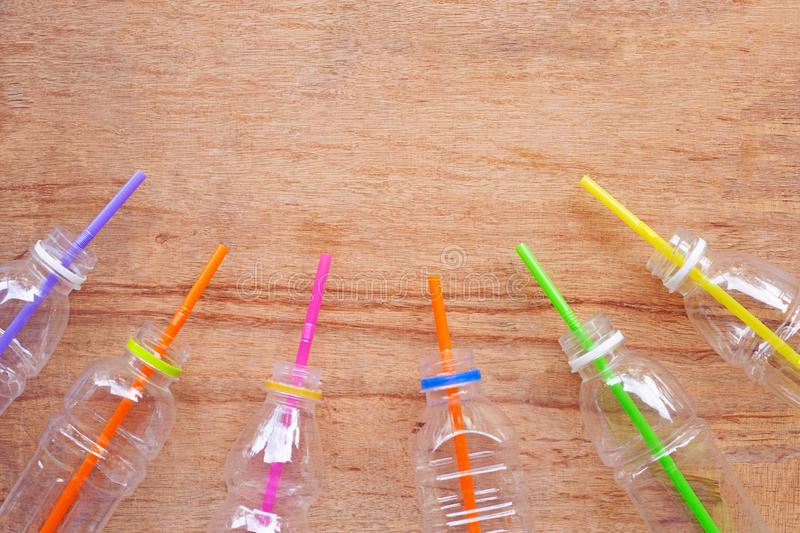Plastic waste, Plastic bottles with straws. On wooden background royalty free stock images