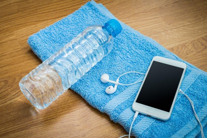 Plastic waterfles, oortelefoons, slimme telefoon en handdoek op wo royalty-vrije stock afbeelding