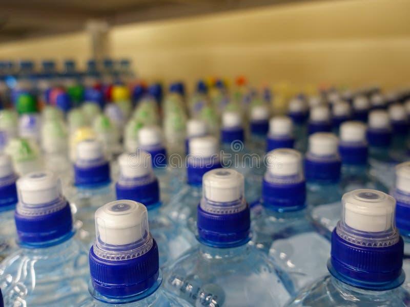 Plastic waterflessen met kappen van verschillende kleur stock foto