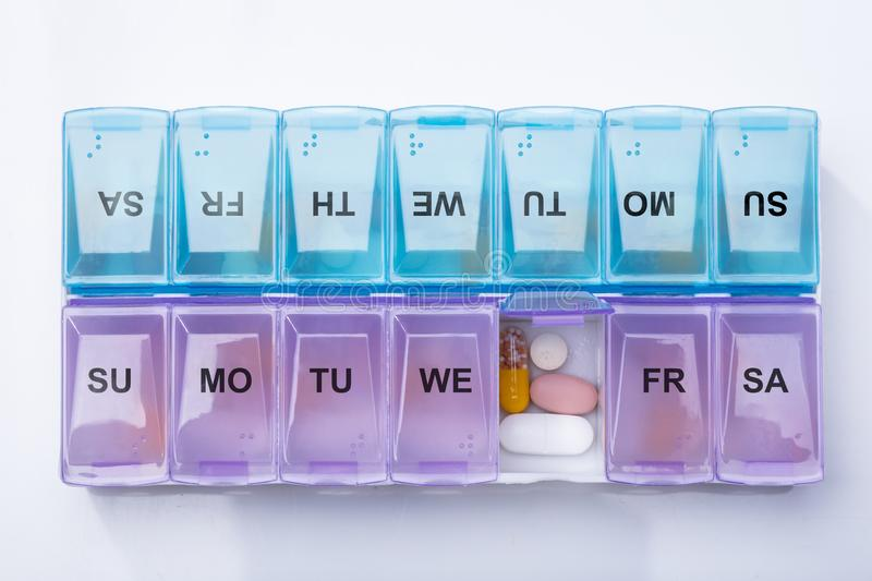 Plastic Weekly Pill Box. Pink Plastic Pill Organizer Shot And Medical Pills On White Background royalty free stock photography