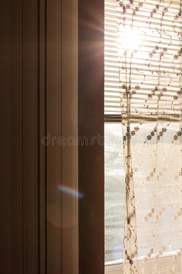 Plastic window with blinds and curtains with rays of sun stock photos