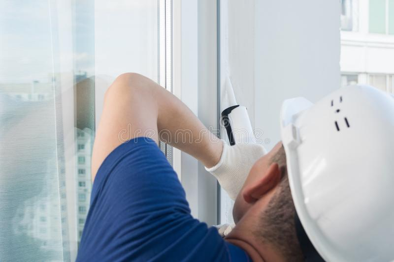 Plastic window installation wizard  closes the seams with silicone in the window stock photography