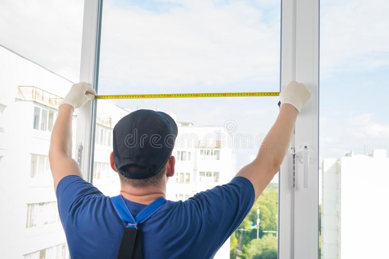 A plastic window installation worker measures the light opening of a window using roulette stock photos