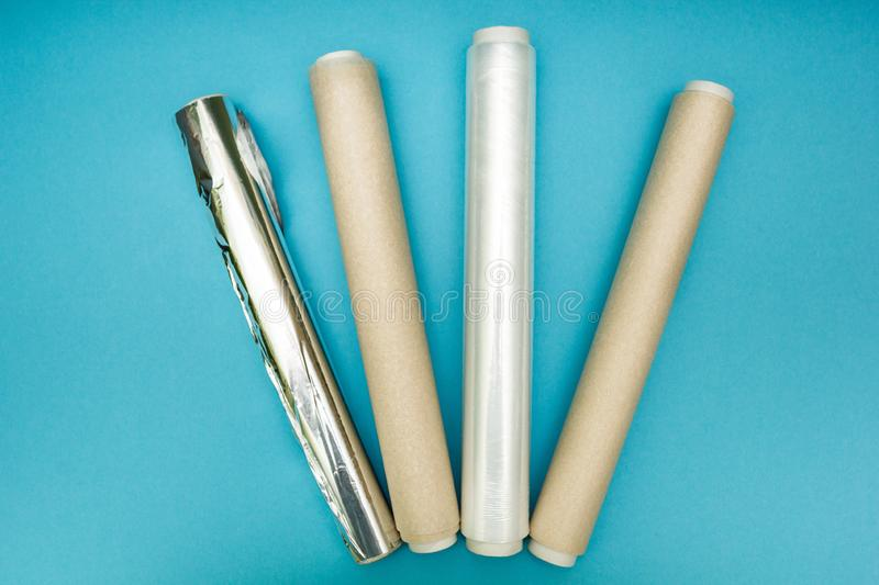 Plastic wrap, aluminum foil and roll of parchment paper on blue background stock images