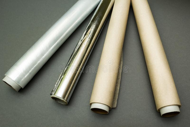 Plastic wrap, aluminum foil and roll of parchment paper on grey background stock photo