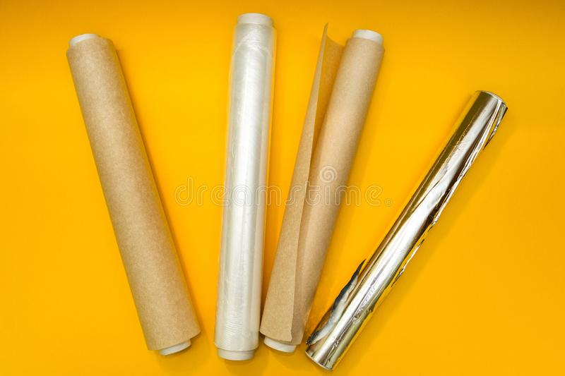 Plastic wrap, aluminum foil and roll of parchment paper on yellow background royalty free stock image