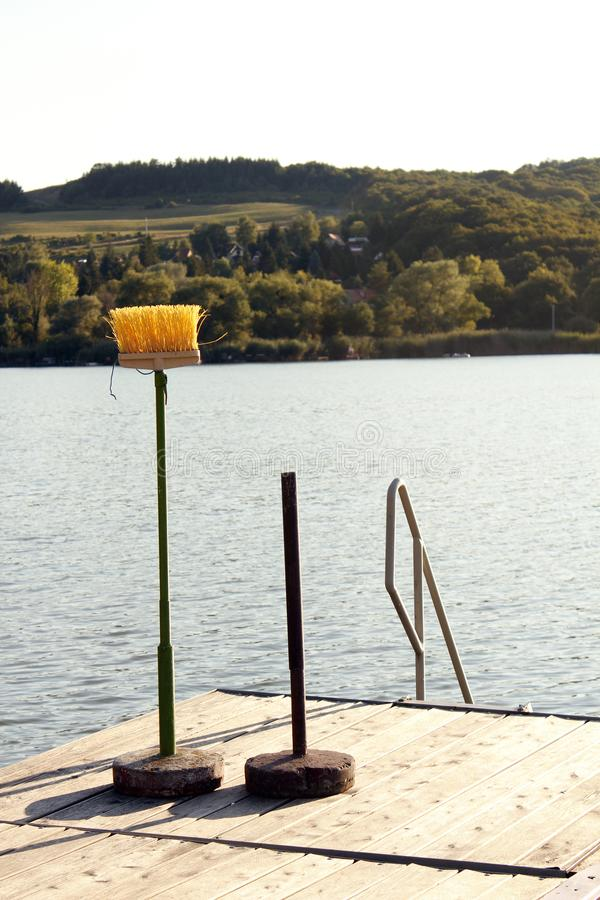 A plastic yellow floor brush instead of an umbrella on wooden platform by the lake. Practicality, misuse, or imperfect relationships, combat with environmental stock image