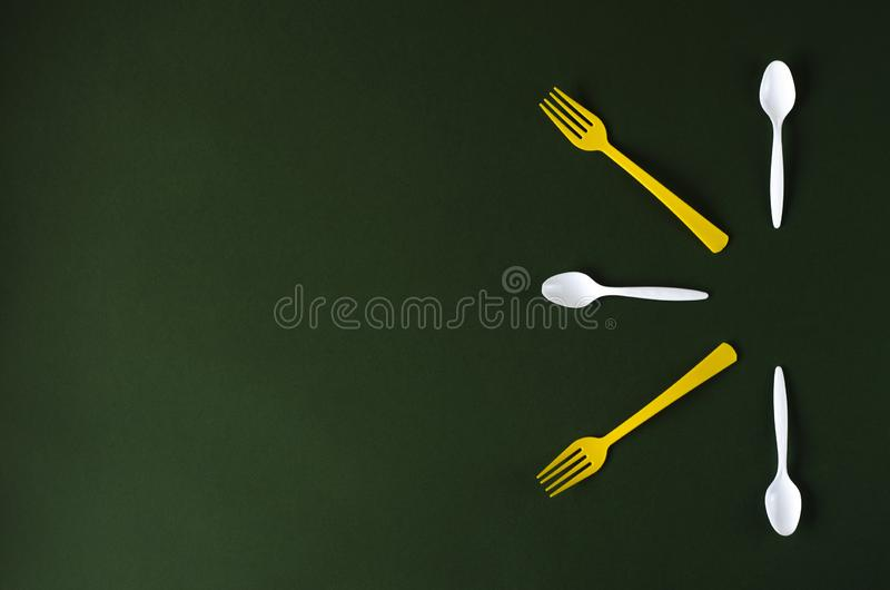 Plastic yellow forks and white spoons on a green background. royalty free stock image