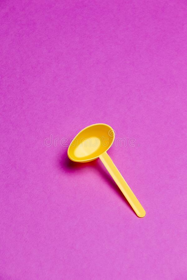 Plastic Yellow Spoon Over Pink Background royalty free stock photo