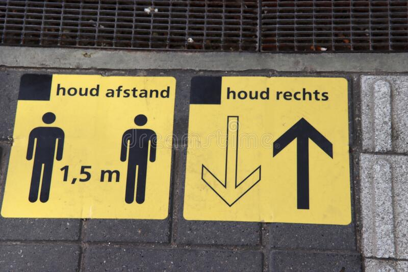 Plastic yellow sticker with in dutch language 1,5 meter Afstand to keep people on distance and keep right on railway station due royalty free stock photography