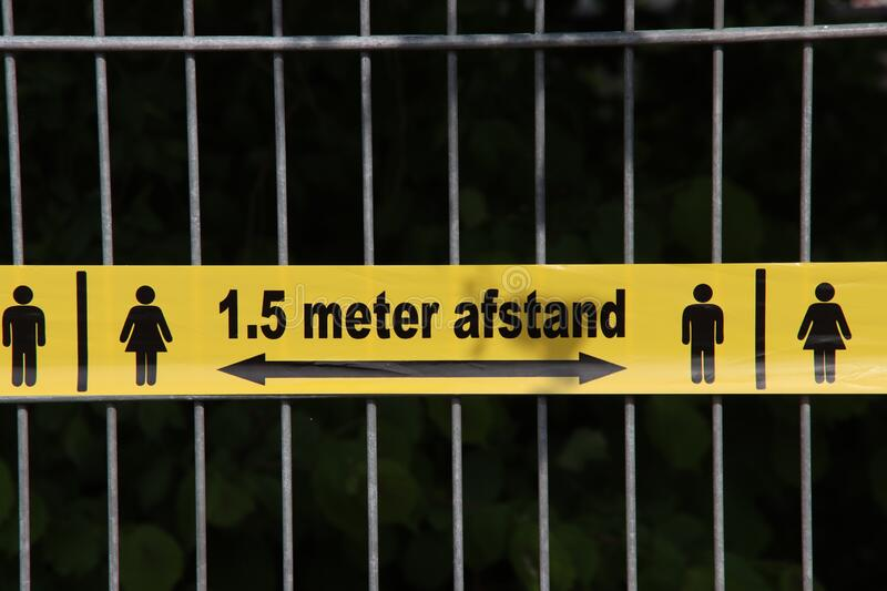 Plastic yellow tape with in dutch language 1,5 meter Afstand to keep people on distance due to the corona covid-19 crisis royalty free stock images