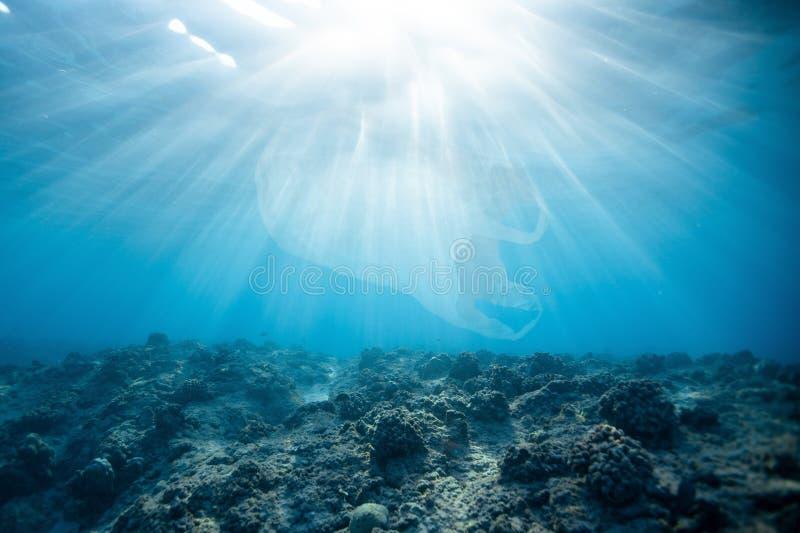 Plastic zakverontreiniging in blauwe oceaan stock fotografie
