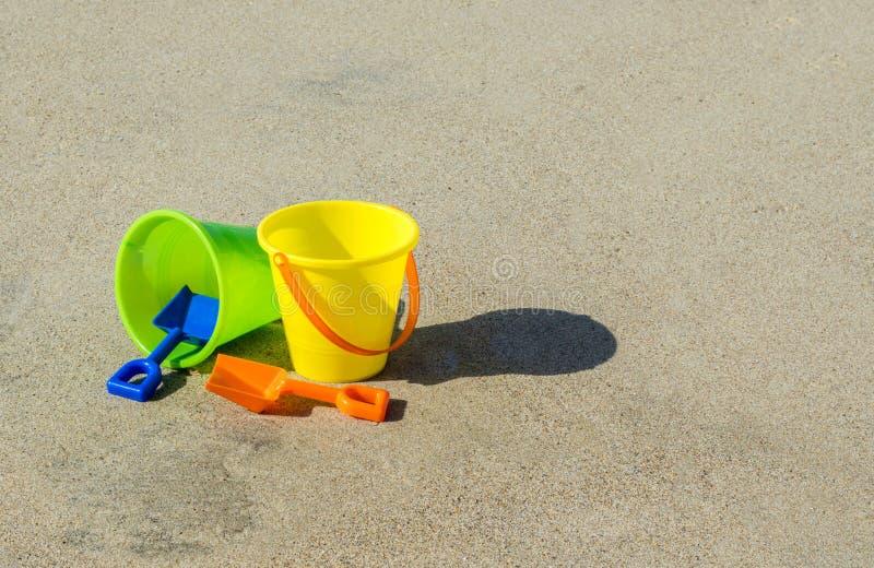 2 plastic zandemmers en schoppen op een vlot zandig strand stock fotografie