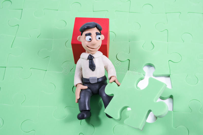 Plasticine businessman collects a puzzle royalty free stock photography