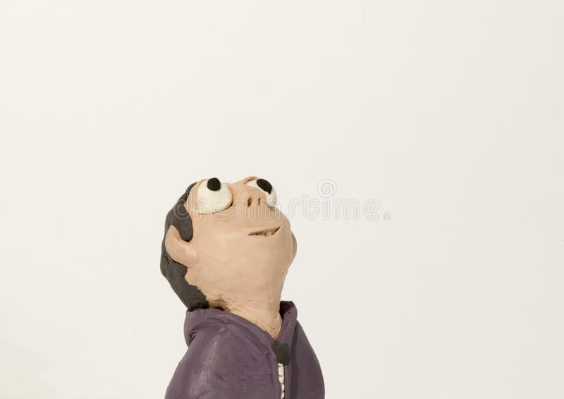 Plasticine character. Boy looking up stock image