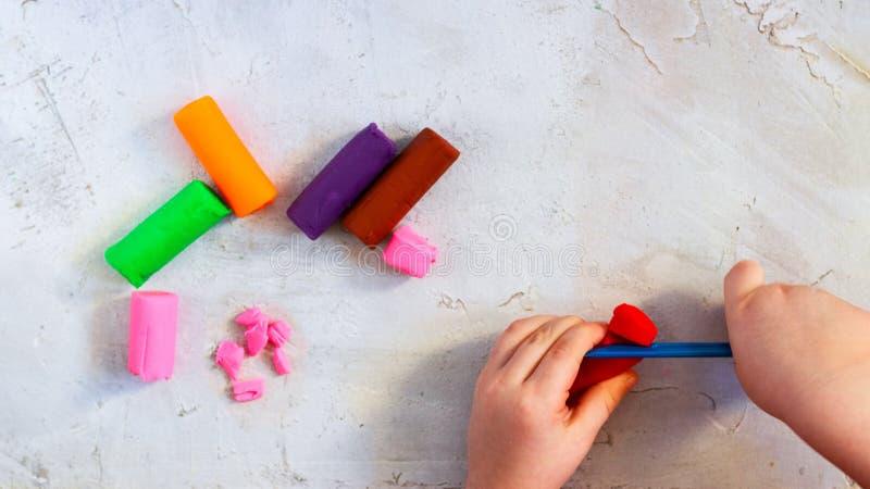 Plasticine colorido da argila, modelando partes da argila com as mãos da criança, horizontais, educação, psicologia de criança foto de stock royalty free
