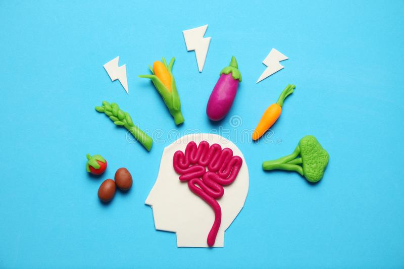 Plasticine figure of man and vegetarian food. Food for mind, charge of energy. Healthy lifestyle, detoxification and antioxidants.  stock photos
