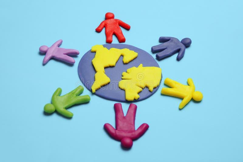 Plasticine figuren van mensen van verschillende rassen zijn op aarde Diverse interacties, communicatie en globalisering stock fotografie