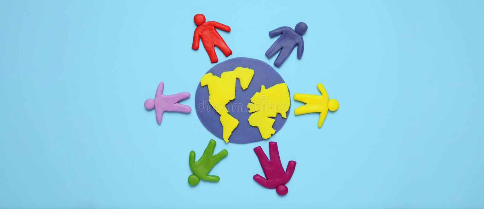 Plasticine figurines of people of different races are on planet earth. A variety of interactions, communication and globalization royalty free stock photos