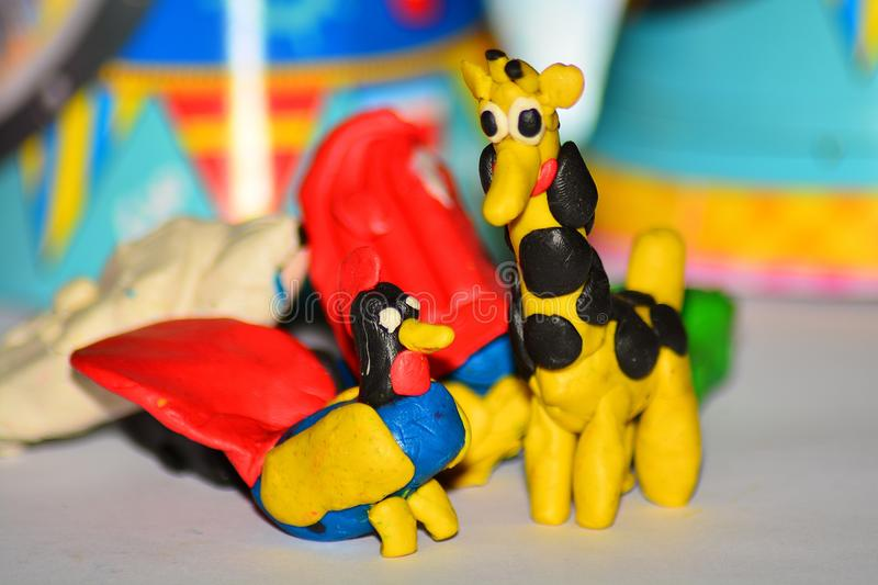 Plasticine giraffe and a rooster stock photography