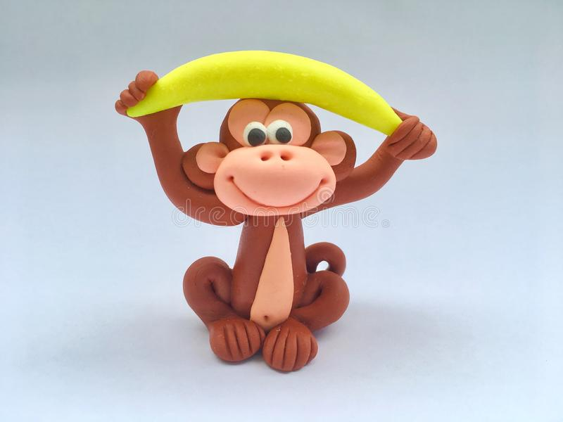 Cute colorful monkey is lifting yellow banana on his head cartoon made from clay on white background in healthy concept. Plasticine, handmade, kid, mascot royalty free stock photography