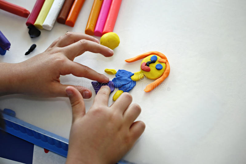 Plasticine. Hands of little girl making doll from colorful clay dough (plasticine stock photos