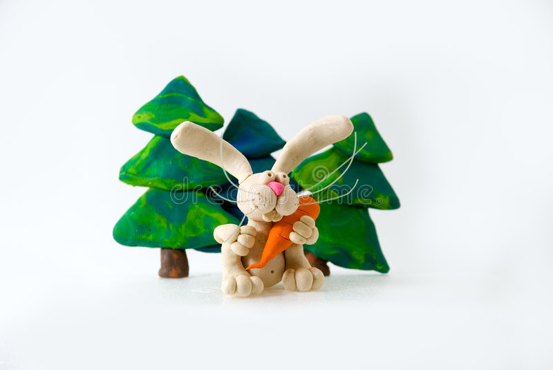 The plasticine hare holds carrots. Near fur-trees royalty free stock image