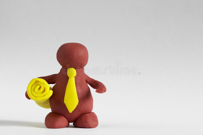 Plasticine man. Keeping a yellow roll over grey background stock photography