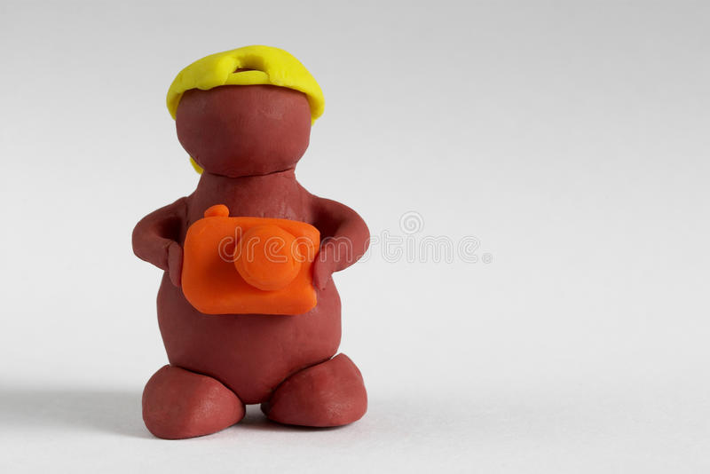 Plasticine man. Keeping the camera over grey gradient background stock photography