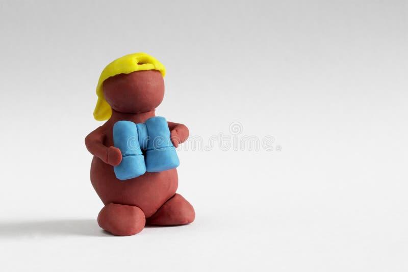 Plasticine man. Keeping the blue binoculars over grey gradient background stock images