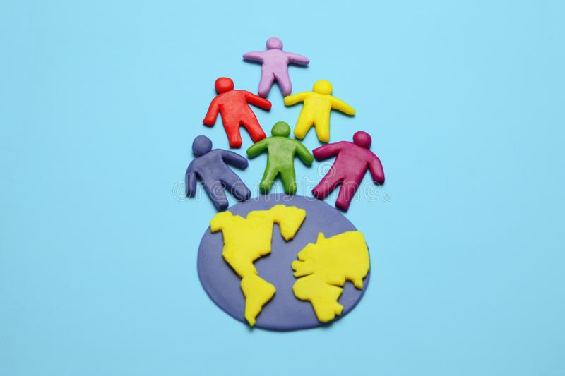 Plasticine multicolored cartoon people on globe. The use and depletion of the planet earth, overpopulation and population growth.  stock photos