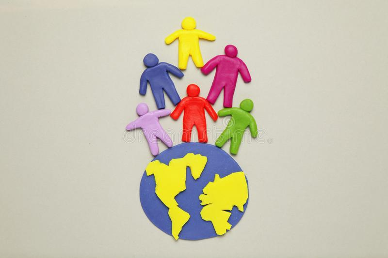 Plasticine multicolored cartoon people on globe. The use and depletion of the planet earth, overpopulation and population growth royalty free stock image