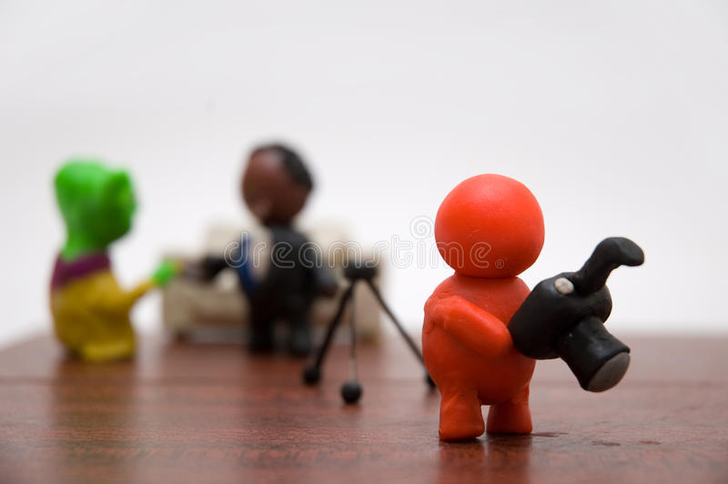 Plasticine person with businessman and alien. Plasticine photographer take a shot of businessman and aliеn stock images