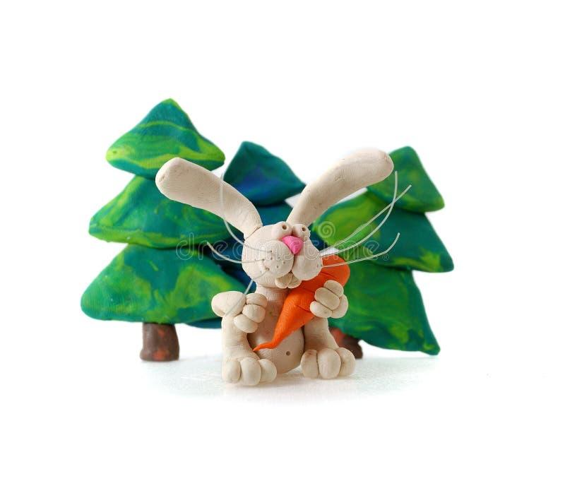 Plasticine rabbit. Plasticine rabbit with carrot against fir-trees stock photography