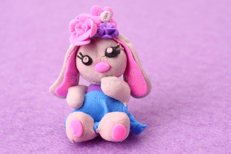 plasticine rabbit on pink background. modelling clay stock photo