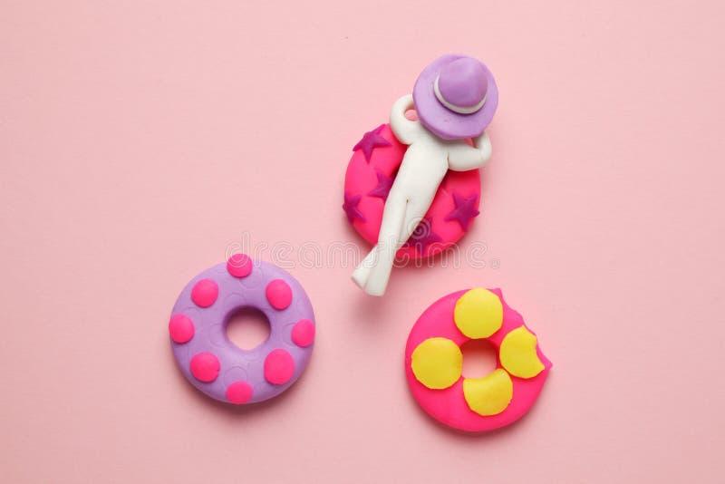 Plasticinemensen die op opblaasbare doughnutlilo ontspannen in pool Het ontspannen en de vakantie van de beeldverhaalzomer stock fotografie