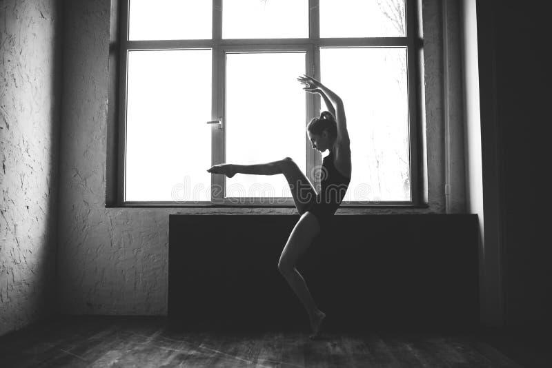 Plasticity slim woman dancing near window. Professional dancer enjoy dance. Lady Dancer Training Modern Ballet In Class. royalty free stock photo
