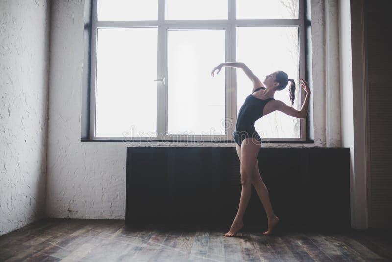 Plasticity slim woman dancing near window. Professional dancer enjoy dance. Lady Dancer Training Modern Ballet In Class. stock photography