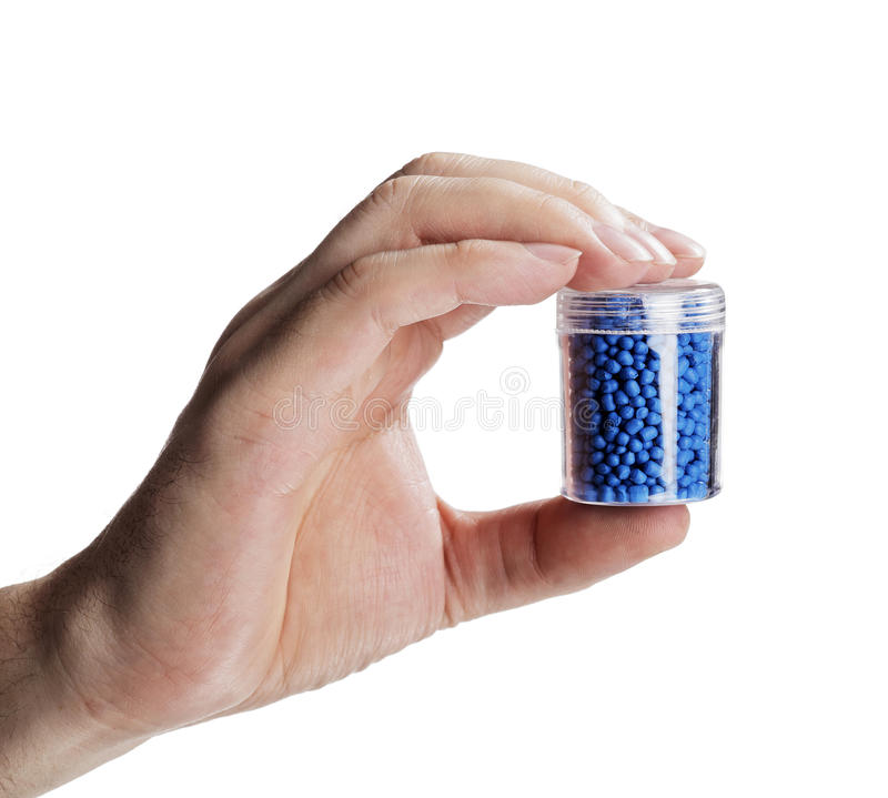 Plastics. Man holding a small container with blue plastic granules, used for manufacturing stock photos