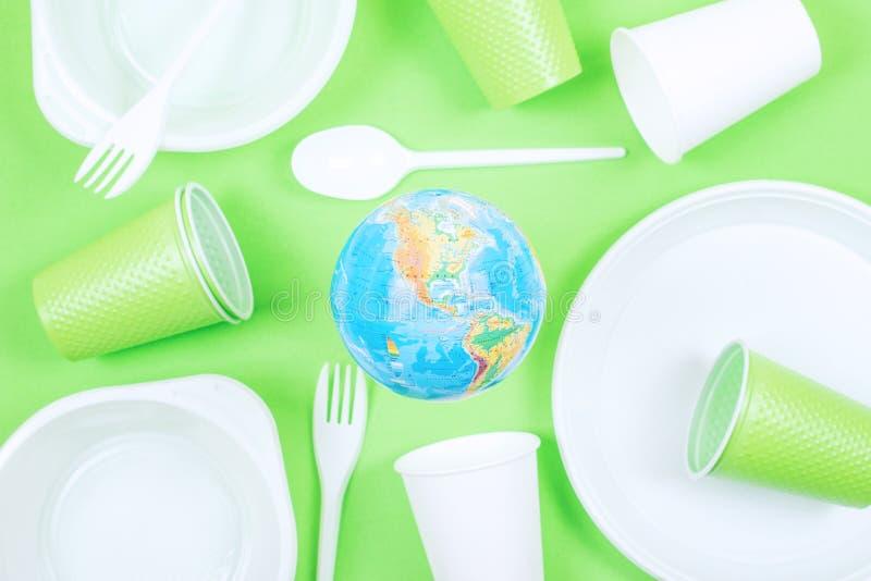Plastiek, verontreiniging, Ecologie, recyclingsconcept Plastic beschikbare vaatwerk en aardebol op groene achtergrond royalty-vrije stock foto