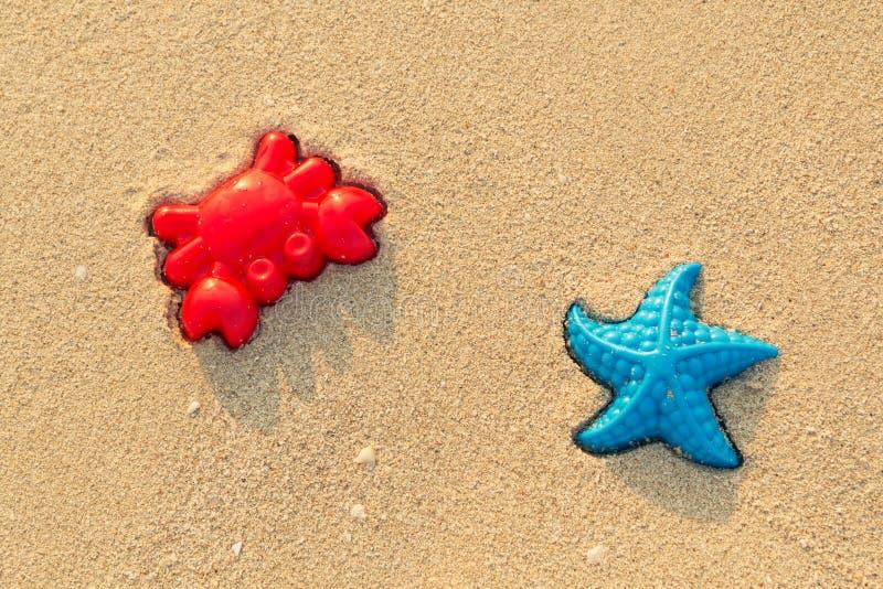 Plastik färbte Formen für Kinderspiel mit Sand auf dem Strand Babyplastik formt das Lügen im Sand auf dem seabeach lizenzfreie stockbilder