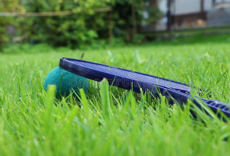 Plastik-softtenis Schläger versteckt im Gras nach magischem Spiel zwischen zwei Jungen Detail für grünen und blauen speziellen Ba stockbild